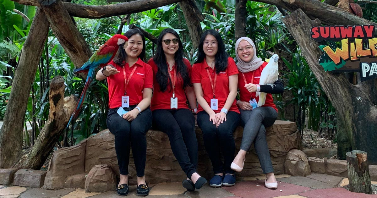 Donned in Sunway signature red polo, the four ladies who make up Sunway Group Sustainability Department sit side-by-side, posing with the parrots at Sunway Lagoon Wildlife Park during daytime