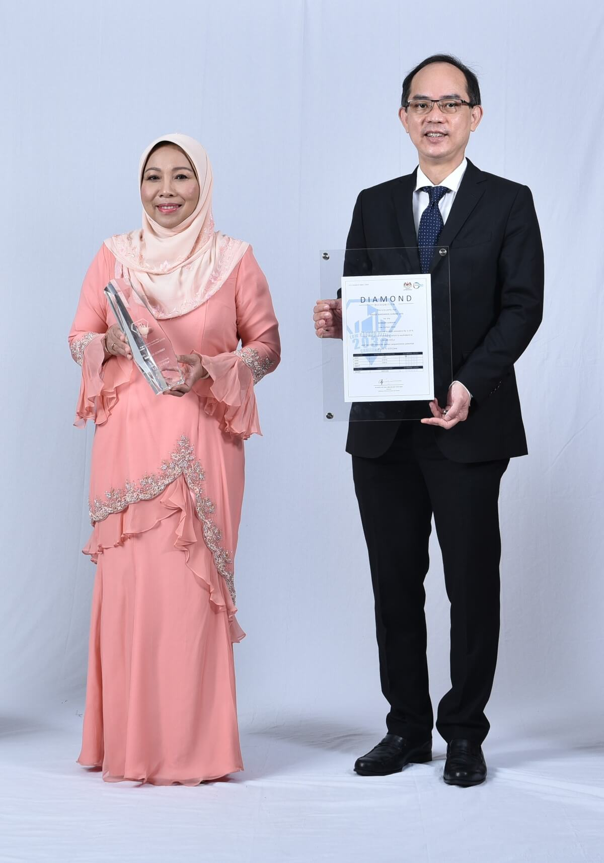 Mayor of Subang Jaya Noraini Binti Roslan and Sunway Property Management Division Senior General Manager holding the Low Carbon City Diamond Recognition trophy and certificate respectively